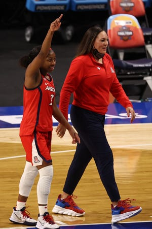 Apr 2, 2021; San Antonio, Texas, USA; Arizona Wildcats guard Aari McDonald (2) and Arizona Wildcats head coach Adia Barnes (right) react while walking off the court after defeating the UConn Huskies in the national semifinals of the women's Final Four of the 2021 NCAA Tournament at Alamodome. Mandatory Credit: Troy Taormina-USA TODAY Sports
