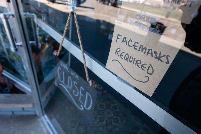 A sign asking customers to wear a mask hangs on the door of a Lexington business.