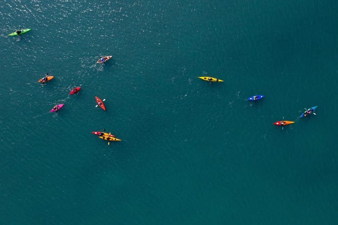 A group of kayakers with Slow Row Michigan paddle a river in St. Clair County.