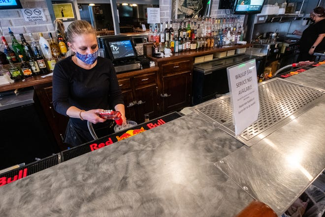 Laura Detary, a server at Steis's Village Inn in Lexington, fills a pitcher of water Tuesday, April 13, 2021. A sign posted on the bar tells customers that walk-up service isn't available due to COVID-19 restrictions.