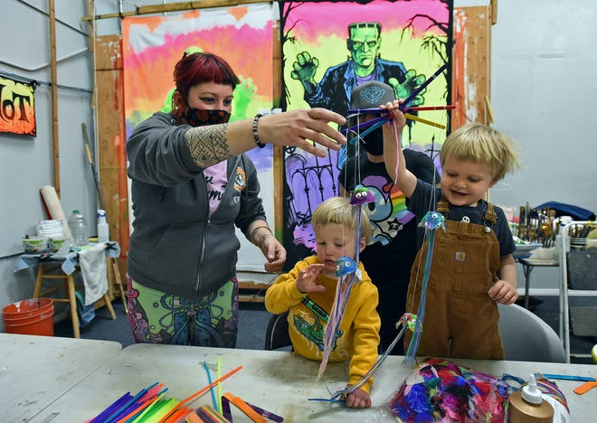 In kid's craft area at the new Generator, Jessi Janusee, left, hands Cassiby Medina, 1, center, and Merlin Tibbetts, 3, a jelly fish puppet, which will be a project children will be able to make during the grand opening of the Gernerator on May 1, 2021.  Alysia Dynamik  stands in the background.