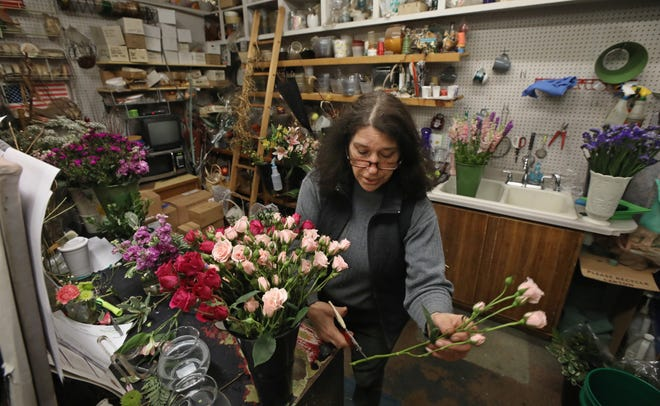 Owner Kim Wilson works on a flower arrangement at Expressions Flowers and Gifts on Merchants Road in Rochester Thursday, April 15, 2021.