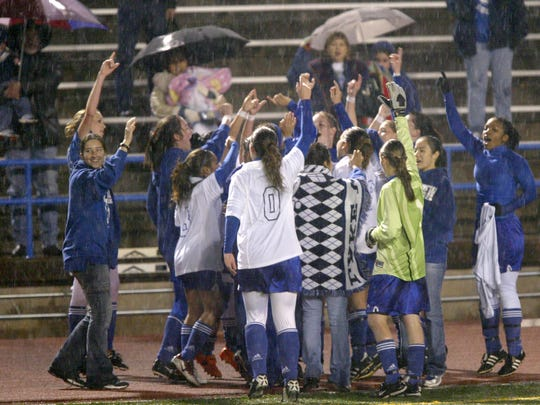 The Lake View Maidens soccer team celebrates a win in the rain after a 2013 game.