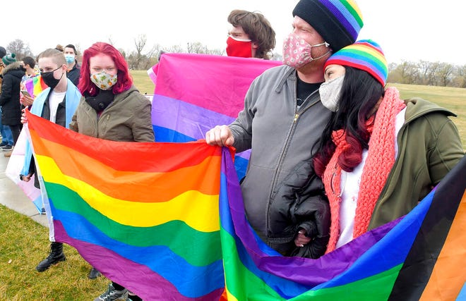 Members of the Olsen and Thorell family hold pride flags during a rally in support of LGBTQ students at Ridgeline High School, Wednesday, April 14, 2021, in Millville, Utah. Students and school district officials in Utah are outraged after a high school student ripped down a pride flag to the cheers of other students during diversity week. A rally was held the following day in response to show support for the LGBTQ community. (Eli Lucero/The Herald Journal via AP)