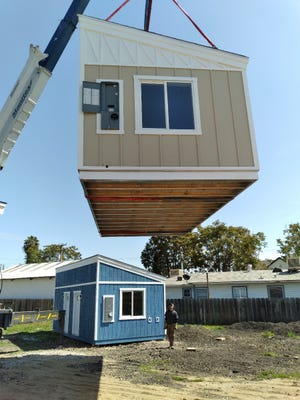 288-square-foot prefab units are craned into a lot on H Street in Tulare. The site will be a community for people experiencing homelessness in Tulare.