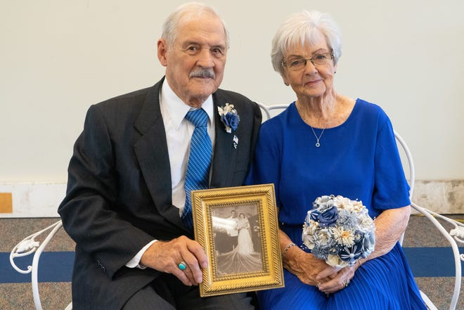 Dick and Bernie Gutridge hold the photo from their wedding taken on April 8, 1951.