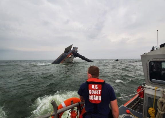 A Coast Guard crew member searches for survivors near the capsized SeaCor Power on Thursday, April 15, 2021.