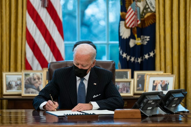 President Joe Biden signs an Executive Order reversing the Trump-era ban on transgender individuals serving in military, in the Oval Office of the White House, Monday, Jan. 25, 2021.