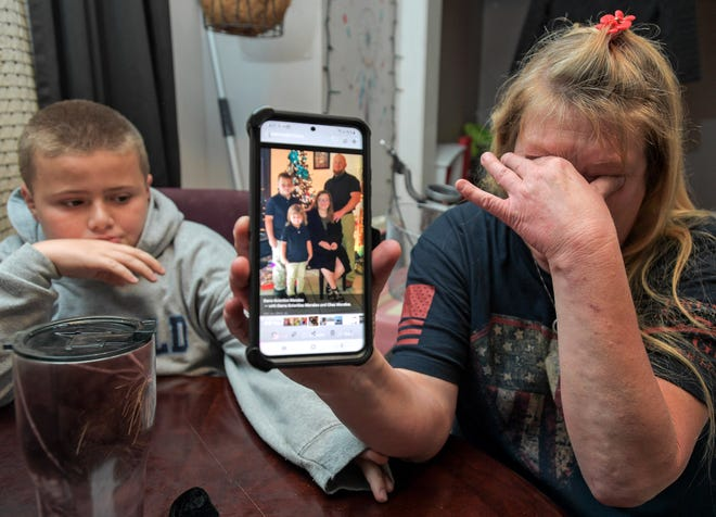 Darra Ann Morales, right, shows a photo of her son Chaz Morales and his family on her phone, as Chaz Jr. comforts his grandmother at their home in Slidell, La., Wednesday, April 14, 2021.
