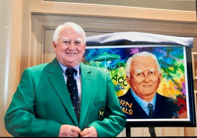 Carey Alexander Washington wearing his tennis official jacket in front of a portrait honoring his 2010 induction into the South Carolina Tennis Hall of Fame.