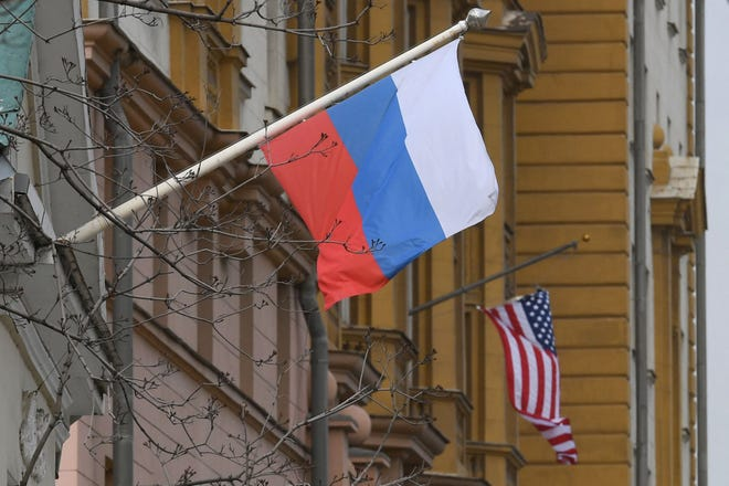 A Russian flag flies next to the U.S. Embassy building in Moscow on April 15. The United States announced economic sanctions against Russia and the expulsion of 10 diplomats in retaliation for what Washington says is the Kremlin's election interference, a massive cyberattack and other hostile activity.