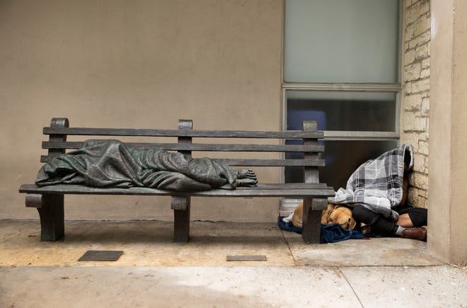 """A homeless man sleeps in a doorway at Central Presbyterian Church on April 16, next to """"Homeless Jesus,"""" a bronze sculpture by Canadian artist Timothy Schmalz."""