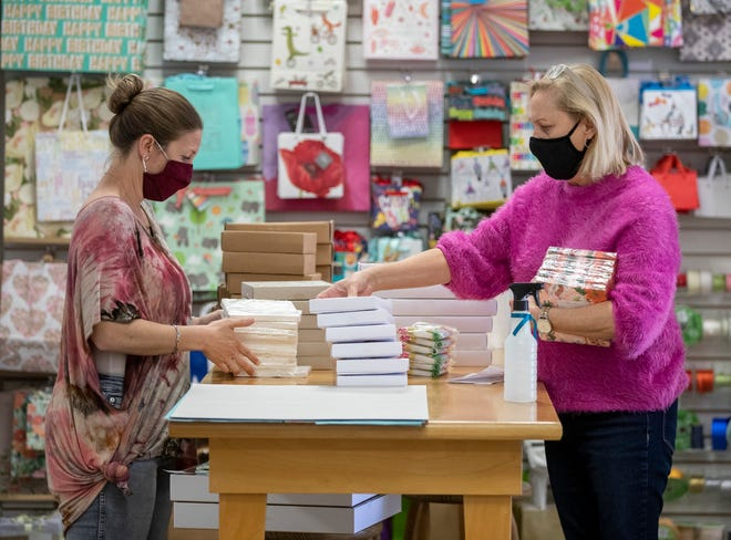 Floor manager Casey Langford, left, and owner Suzy Ranney, stock shelves at Paper Place in April. The Austin area unemployment rate fell from 5.6% in February to 5.3% in March.