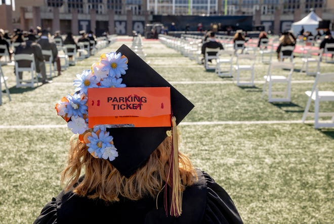 Texas State University graduate Anne Cox wears a mortarboard decorated with a parking ticket at a commencement ceremony at Bobcat Stadium in San Marcos on December 10, 2020.