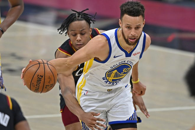 Golden State Warriors guard Stephen Curry (30) drives against Cavaliers forward Isaac Okoro during the Warriors'119-101 win Thursday night in Cleveland. [David Dermer/Associated Press]