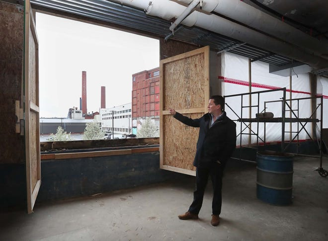 Osborne Capital President Lance Osborne looks out over the view of the Goodrich smokestacks Friday as he talks about renovating Canal Place buildings 10-17 in Akron and putting in apartments and a section for retail.