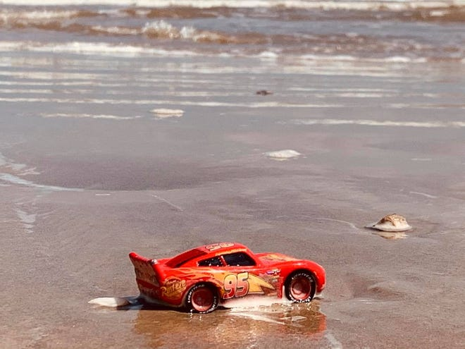 A toy race car sits on the beach as waves come slowly rolling in.