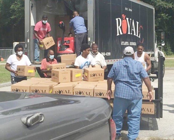 Volunteer unload boxes of food to be distributed locally.