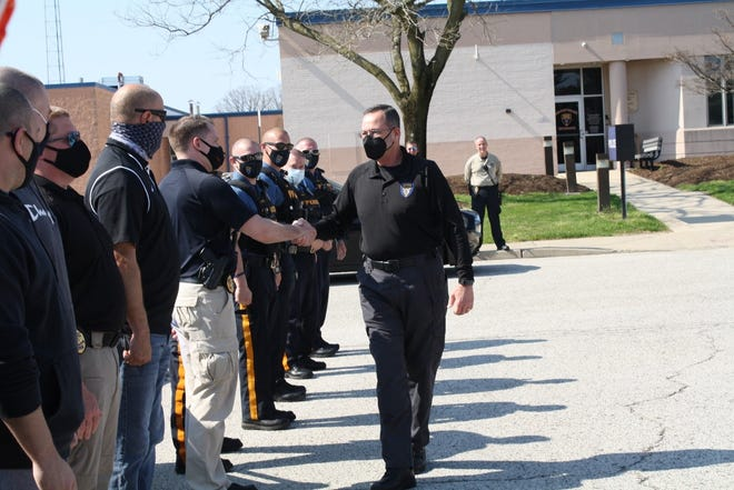 Chief Alfonso Parente Jr. walks down a line of officers during his radio sign-off ceremony on April 7.