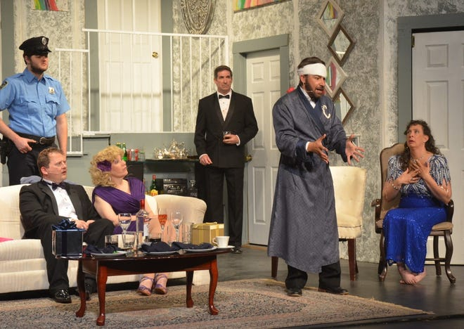 """Six of the 10 performers cast in the Lyric Theatre's production of Neil Simon's  """"Rumors"""" are in either their first or second Lyric show. In this scene from the second act, Lenny Ganz (played by Levi Packer) is wearing a head bandage and robe as he spins a whopper of a tale to explain to police why gunshots were heard during a dinner party. Also pictured, from left to right, are Officer Welch (played by Jake Bowren), Ken Gorman (played by Nicholas Ewen), Chris Gorman (played by Tommie Bailey, in her first Lyric show), Glenn Cooper (played by Joseph Dennis), and Claire Ganz (played by Lasha Dennis). Jake Bowren, Levi Packer, and Lasha Dennis are making their second appearances on the Lyric stage. Neil Simon's """"Rumors"""" opened Friday night, and the run continues with a matinee Sunday afternoon and four shows next weekend."""