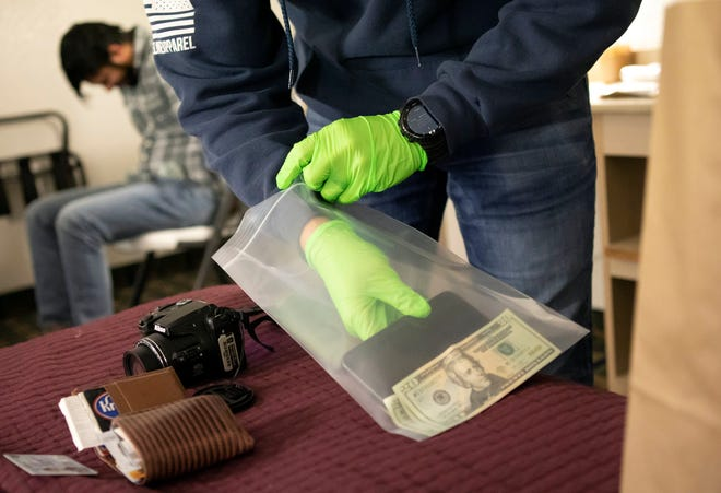 A man sits in handcuffs while he has his possessions searched and money and cellphone confiscated as Hilliard and Grove City police carry out a prostitution sting called Operation 614 at a Hilliard-area motel on Thursday.