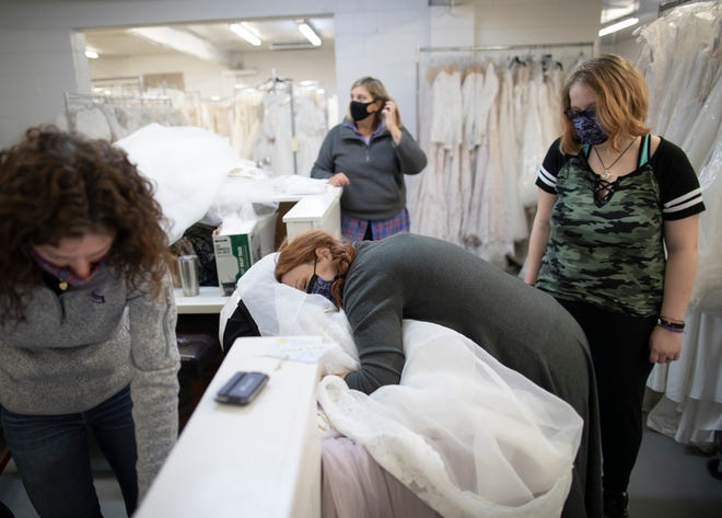After a 30-minute dash to sort through some of more than 8,500 dresses, Madison Osborne, 14, right, watches as her mother, Elizabeth Beckwith, 37, of Grove City, hugs her new wedding dress Friday as she checks out with program coordinator Lacey Wicksall, left, during a dress sale for Wish Upon a Wedding.