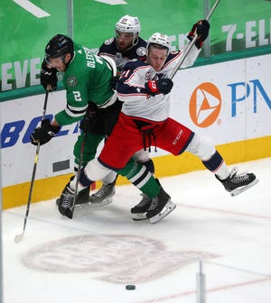 Blue Jackets rookie Josh Dunne (21) battles Dallas defenseman Jamie Oleksiak for the puck in his NHL debut on Thursday while his Columbus teammate Stefan Matteau trails the play.