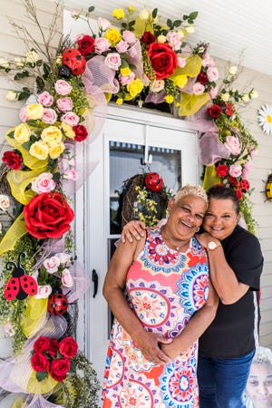 Kathy Austin and Angela Boudreaux stand outside Austin's decorated front door on Lafayette Street in Houma. They've been working together for years, and their designs are a collaborative effort.