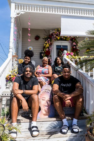Kathy Austin's grandkids sit with her on the porch. In the back row (from left) are  Jayden Austin, Kathy Austin and Jordan Austin. In the front, Kane (left) and Kani Austin sit beside a photo of Zena Austin their mother, who died in August from complications of diabetes. Messiah Austin is not pictured.