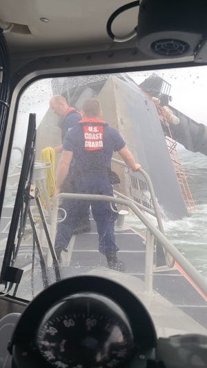 A Coast Guard crew from Grand Isle prepares to throw a heaving line at the hull of the capsized Seacor Power on April 15, two days after the oilfield liftboat capsized about 8 miles off Port Fourchon. The crew was trying to make contact with potential survivors inside the boat but did not get a response.