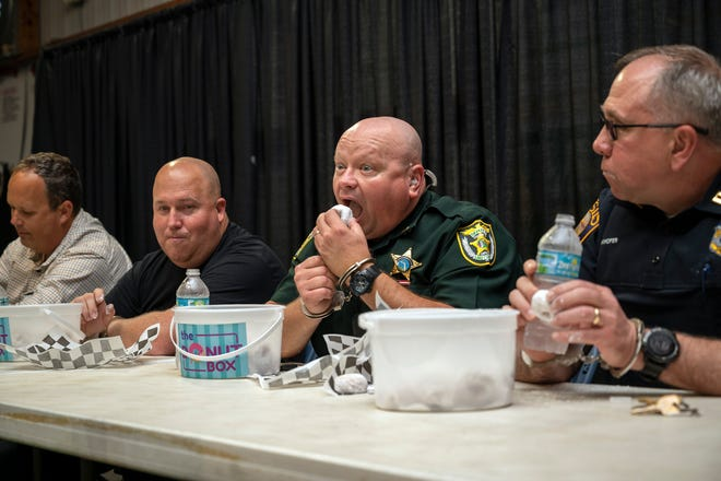"""An officer from the Lake County Sheriff's Office downs a donut at the """"Cuff 'em and stuff 'em"""" law enforcement donut eating contest at the Lake County Fair on Thursday. [Cindy Peterson/Correspondent]"""