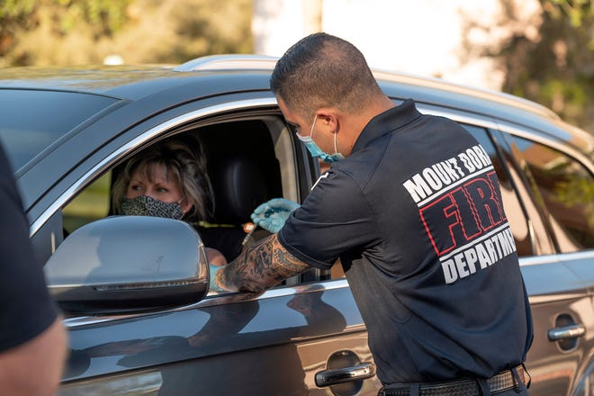 Mount Dora Firefighter and Paramedic Carlos Cervantes administers a COVID-19 vaccine to a Lake County school teacher  in Mount Dora. [Cindy Peterson/Correspondent]