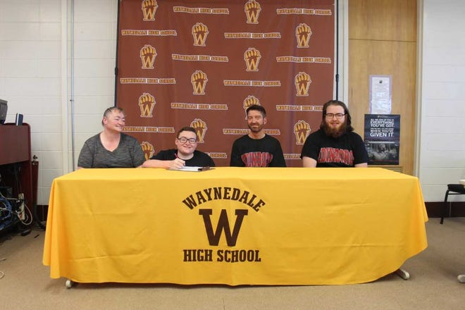 Elijah Yoder (second from left) celebrates signing with Edinboro University of Pennsylvania to play wheelchair basketball in college.