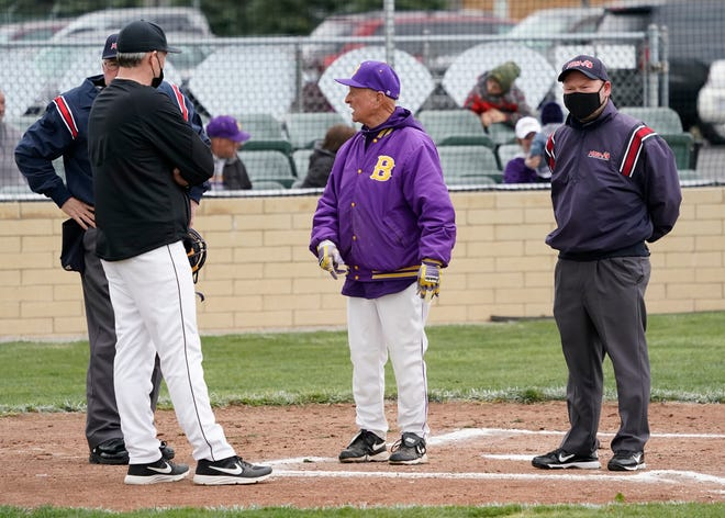 Blissfield head baseball coach Larry Tuttle meets with the umpires and Tecumseh head coach Tom Bullinger prior to Thursday's game in Blissfield.