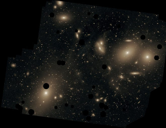 This small portion of the Virgo Galaxy Cluster was photographed by Chris Mihos and his colleagues with the Burrell Schmidt telescope. The dark spots cover bright foreground stars. The largest galaxy shown, at lower left, is M87. Chris Mihos (Case Western Reserve University)/ESO; Creative Commons Attribution 4.0 International License.