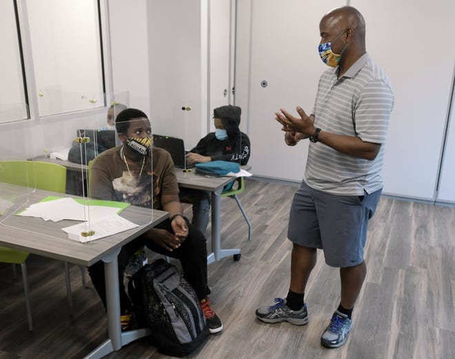 Former tennis professional MaliVai Washington talks with Elijah Thomas, 12, at the after-school program for children at his Club 904 on West Sixth Street on April 15. The youth program is celebrating its 25th anniversary this year.