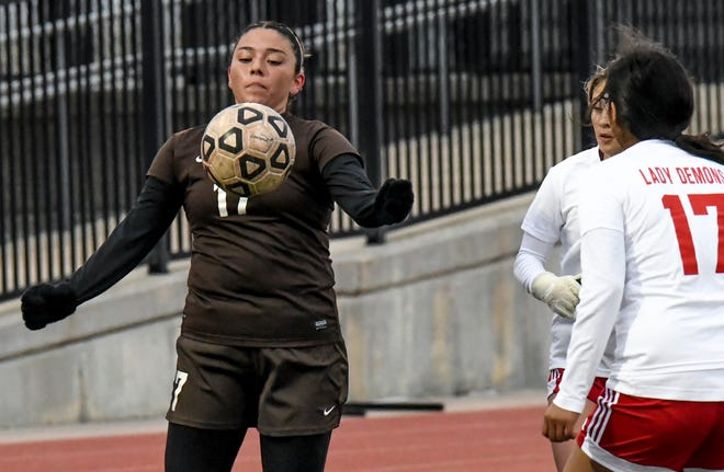Garden City High School's Anahi Castillo, left, takes the ball off her chest to make a steal against Dodge City Thursday at Buffalo Stadium.  The Buffaloes won the WAC contest, 3-2.