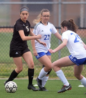 Newton junior Leticia Hernandez, left, is challenged by a pair of Goddard players during play Thursday at Fischer Field. Newton hosts Maize South Tuesday.