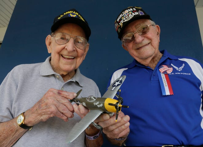 Maj. Jack Hallett, 100, left, and Chief Master Sgt. Mel Jenner, 98, hold up a scale model of Frigid Midgit, Hallett's P-47 fighter bomber, one of two aircraft he flew over Europe during World War II. Jenner was a gunner on a B-17. Hallett flew more than 100 missions.