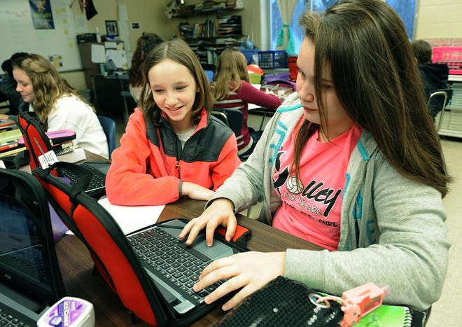 Madison Norton, 11, (left) helps fellow sixth-grader Katelyn Wilkes, 11, with a vocabulary game in language arts in this 2014 photo. In January, 2014, Bedford Junior High School's sixth-graders received Chromebook laptops as part of the rollout of Bedford Public Schools' 1:1 initiative. The 1:1 initiative expanded to Grades 5 and 7 in 2015, to Grades 4 and 8 in 2016 and finally to the high school in 2017.
