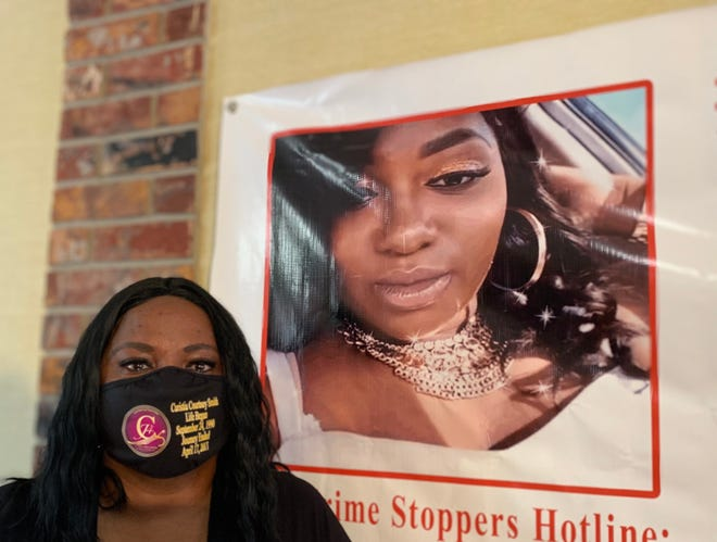 Jacqualine Smith poses by a poster of her late daughter, Curtisia Courtney Smith, at the headquarters for her foundation, Justice 4 Courtney in Lantana on April 16, 2021. In the four years since he daughter was fatally shot in a targeted attack in Boynton Beach she has been hoping for someone to come forward with information as to why her 26-year-old was killed.