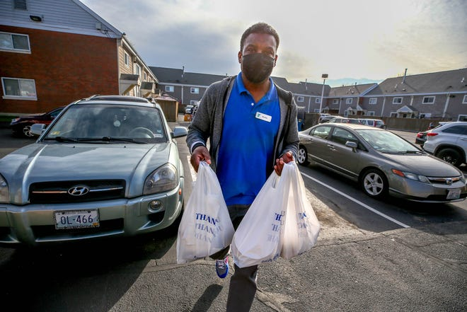 Kyle Dennis delivers bundles of food to residents of the apartments at Wiggins Village, a housing development on Cranston Street in Providence.