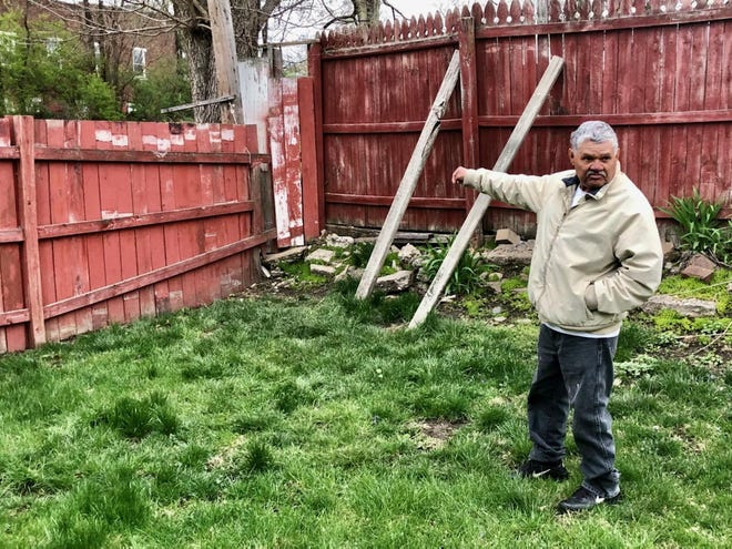 Angel Nunez points Wednesday to the corner of the fencing in the backyard of his Illinois Avenue home where he said a Rockford police officer peered over the fence and shot his grandson who was trying to run away.