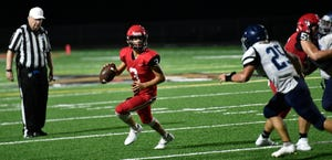 Cardinal Mooney quarterback Tayven Clark rolls out against North Port High last season.