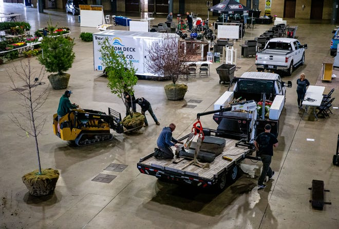 A crew from Paul Tree Farms setups up a Japanese lilac tree as vendors begin setting up for the 30th Annual Spring Lawn & Garden Sale at the Bank of Springfield Center in Springfield, Ill., Friday, April 16, 2021. The event is the first major show held at the BOS Center since the COVID-19 pandemic began last year. [Justin L. Fowler/The State Journal-Register]