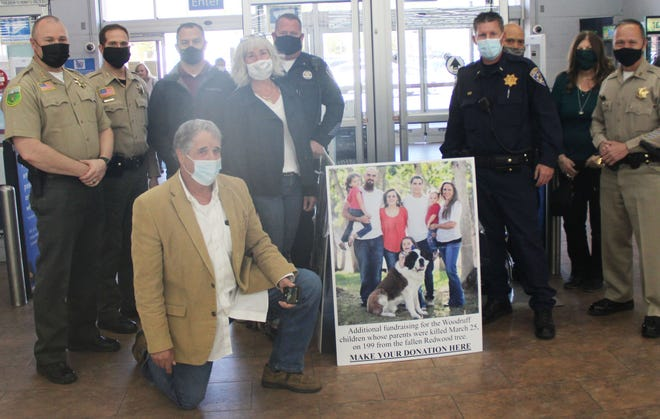Roger Gitlin, shown kneeling, is a retired Del Norte County Board of Supervisors member. He came to Yreka on April 15, 2021 to present a check for more than $3,000 to the Woodruff children, whose parents died last month in a freak accident near Crescent City. Members of local law enforcement and Siskiyou County Supervisor Nancy Ogren came out to show support for this donation and for the Woodruff family.