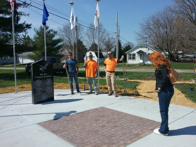 A woman looks for her father's name on Neponset's memorial to veterans as Mike Weeks, Sons of American Legion member, along with city employees Dan Erdman and Trent Johnson, put the final touches on the memorial.