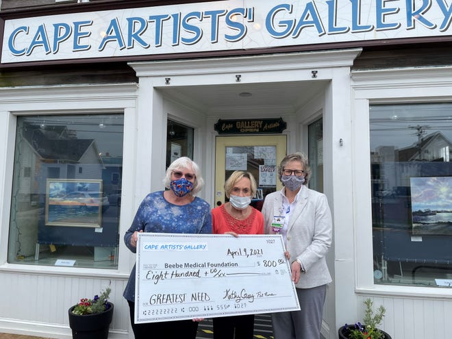 Cape Artist Gallery Chair Kathy Casey and Cape Artist Group President Pat Riordan present their gift to Beebe Medical Foundation Executive Director of Development Kay Young.