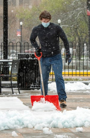 WORCESTER - Dan McColl clears slushy snow outside City Hall Friday. McColl works for the city Department of Public Works & Parks.