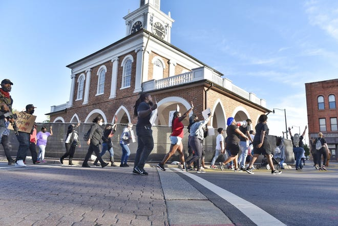 Protesters march around the Market House on Friday. [Ed Clemente for The Fayetteville Observer]